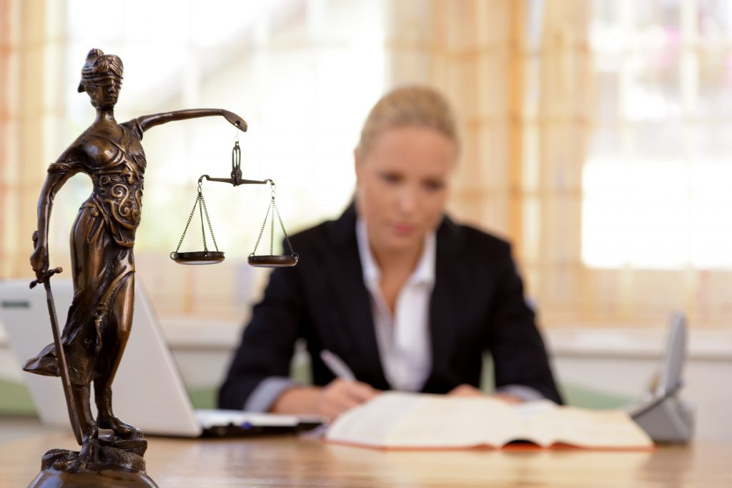 Woman lawyer sitting at desk working on legal case.