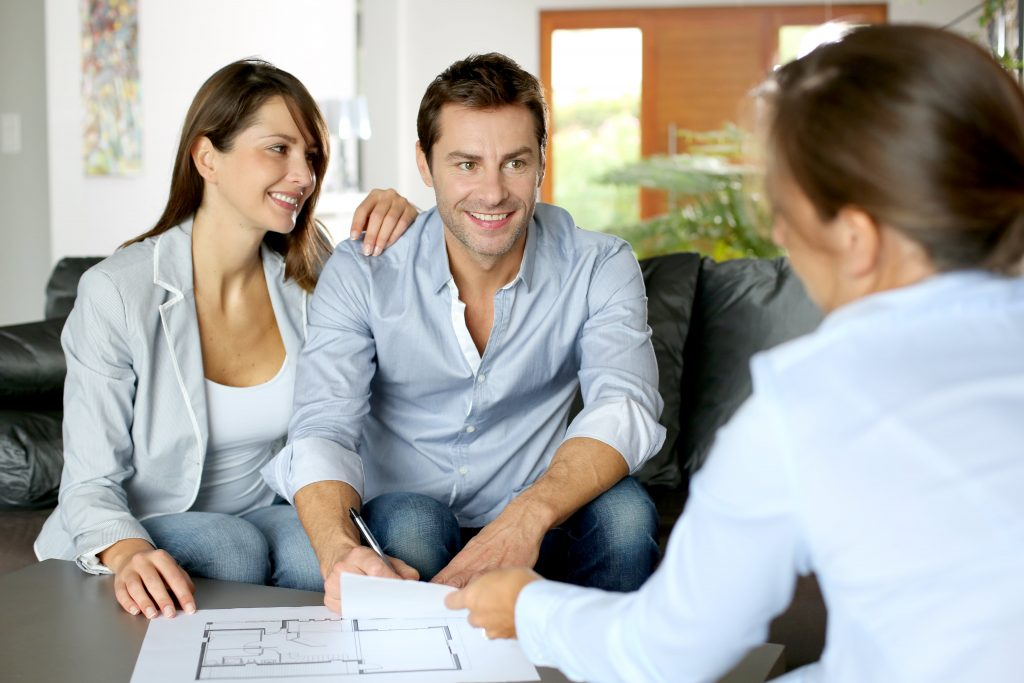 Home buyer couple sitting with real estate lawyer